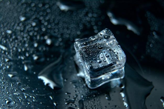 黒の背景に氷のキューブを閉じる/氷を溶かす