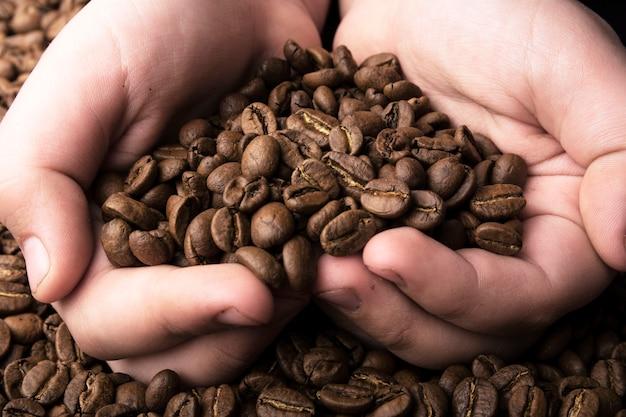 コーヒーの背景に手の中空のコーヒー穀物の中心部。
