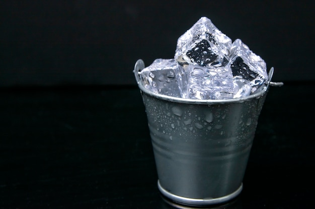 Металлическое ведро шампанского, полное льда. изолированные на черном