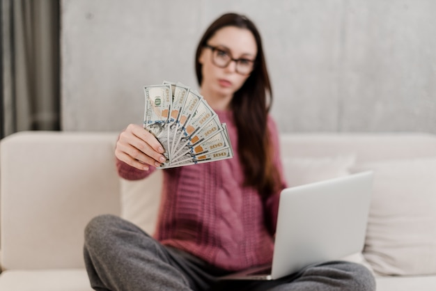 ノートパソコンとソファの上に自宅でお金を稼ぐ女性