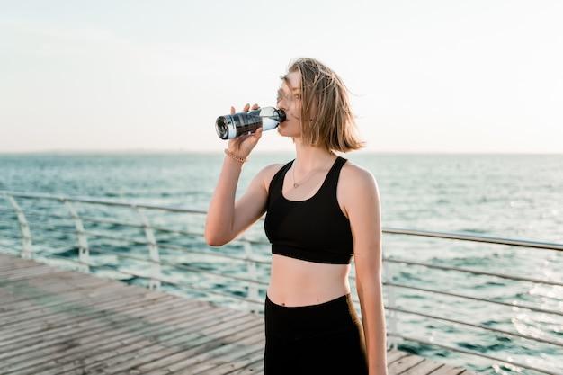 Спортивная девушка-подросток пьет воду на пляже во время тренировки