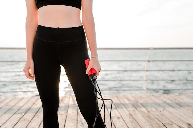 Подходит девушка с скакалка на пляже, осуществляя и работая