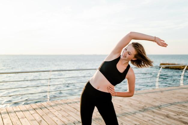 Подходит девочка-подросток, растягивающаяся и занимающаяся фитнесом на пляже