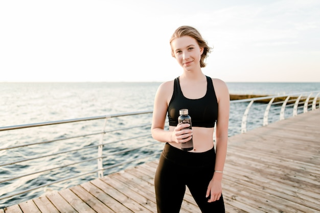 Девушка пьет воду из бутылки во время фитнес-тренировки на пляже