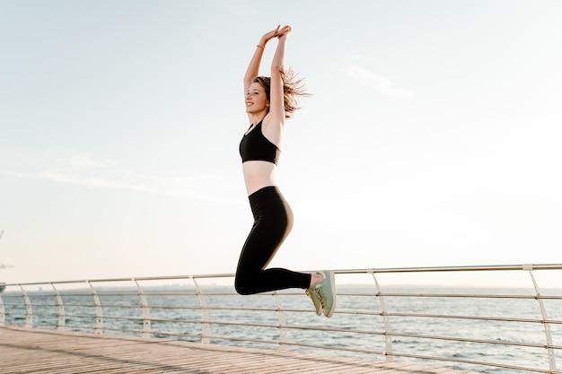 Подходит девушка прыгает высоко в воздухе на пляже