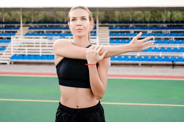 朝はフィットネススタジアムで運動前にストレッチの女性に適合します。
