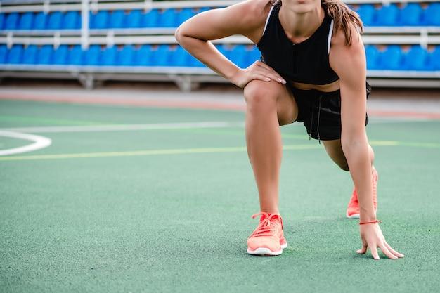 スポーティな女性のフィットネストレーニングを行い、朝スタジアムでワークアウトに合う