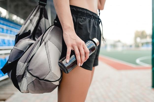スタジアムでスポーツトレーニング中に女性飲料水に適合します。