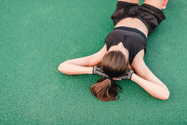 スポーティな女性のトレーニングと午前中にスタジアムでストレッチ