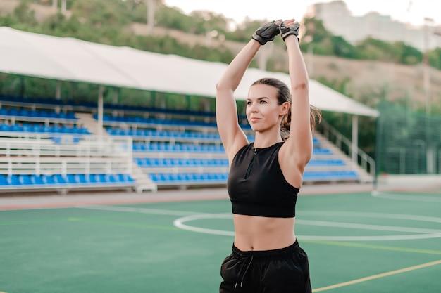 スポーティな女性のトレーニングと朝のスタジアムでのエクササイズ