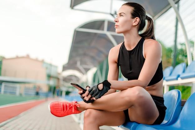 フィットスポーティな女性はフィットネストレーニング中に午前中にスタジアムで携帯電話を使用します