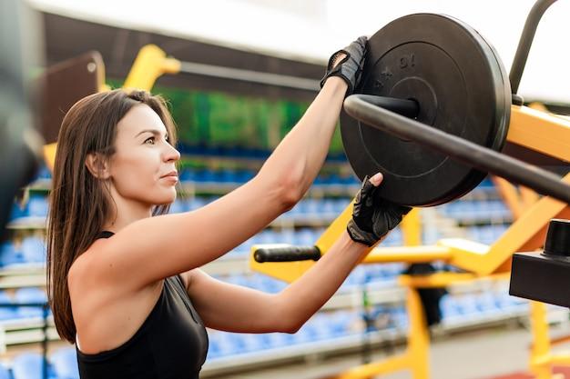 スポーティなフィット女性トレーニングと朝のスタジアムでのエクササイズ