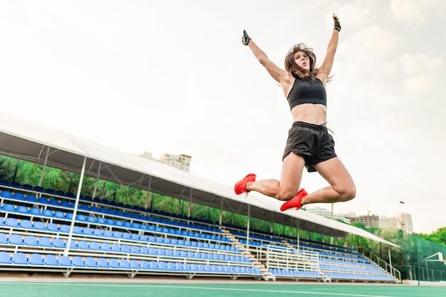 Красивая здоровая спортивная женщина прыгает на стадионе высоко в воздухе