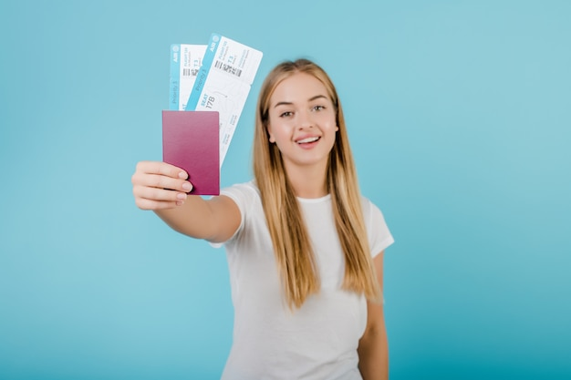 Красивая молодая улыбающаяся белокурая девушка с паспортом и билетами на самолет, изолированными по синему