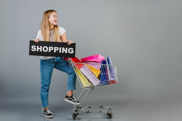 幸せな笑顔の美しいブロンド女性ショッピングサインと手押し車のカラフルなショッピングバッグの完全な
