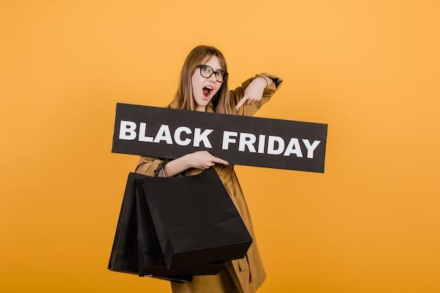Удивленная женщина с черной пятницей и бумажные сумки, изолированные на желтом