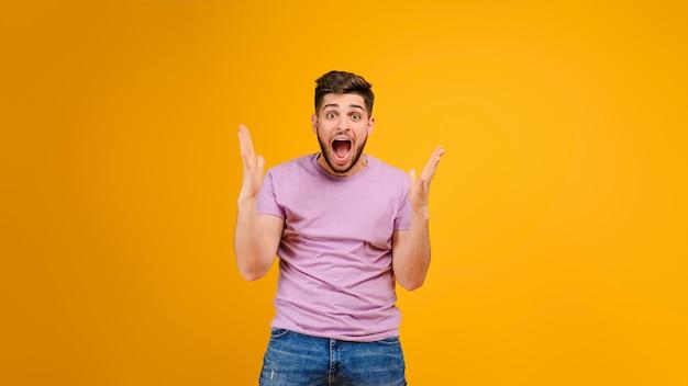 黄色の背景に分離された幸せな悲鳴若い男