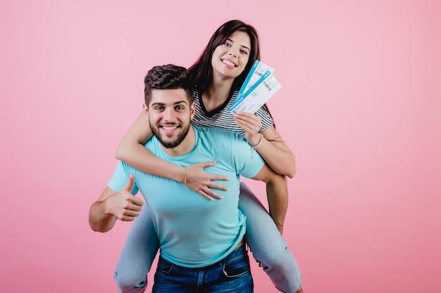 Красивая молодая пара с билетами на самолет, парень держит подругу подражая самолет