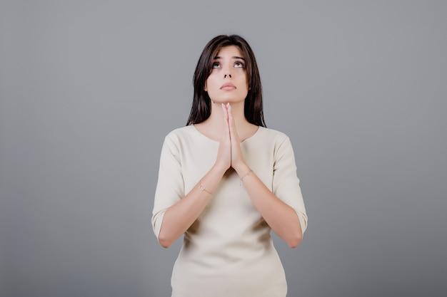 美しいブルネットの女性の祈りと見上げる灰色の分離