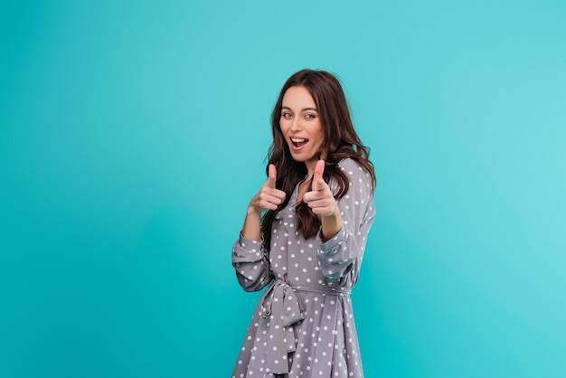 Молодая счастливая усмехаясь женщина указывая изолированные пальцы