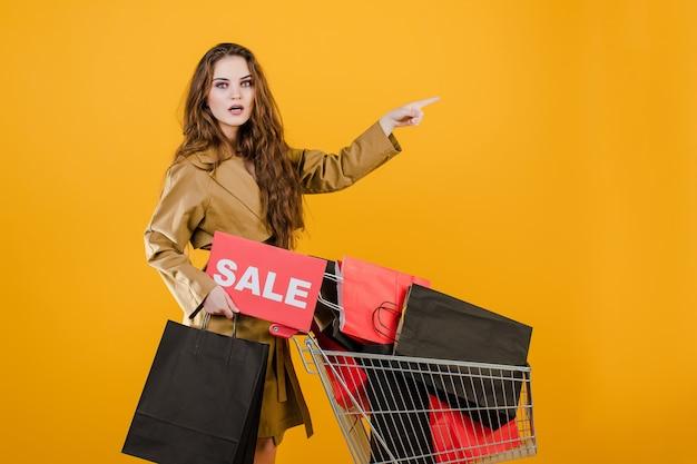Удивленная и взволнованная девушка имеет знак продажи и ручную тележку с красочными сумками и сигнальной лентой, изолированных на желтом