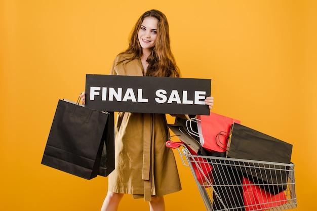 Улыбающаяся молодая женщина имеет знак окончательной продажи и тележку с красочными сумками и сигнальной лентой