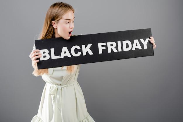 Удивленная милая девушка с черным знаком пятницы изолированная над серым цветом