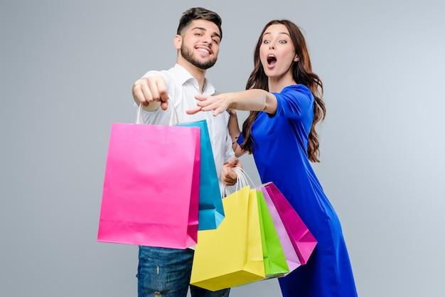 女性は灰色で分離された彼女のボーイフレンドから買い物袋を取得したいです。