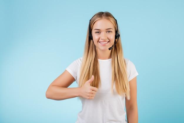 青で分離されたヘッドセットとフレンドリーな笑顔金髪コールセンターオペレーター