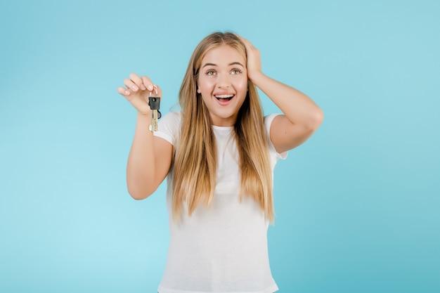 青で分離されたアパートからのキーを持つ幸せな笑顔金髪女性