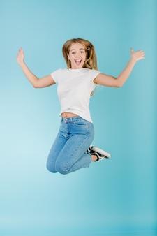 青で分離された空気で高くジャンプ感情的な笑顔幸せなブロンドの女の子
