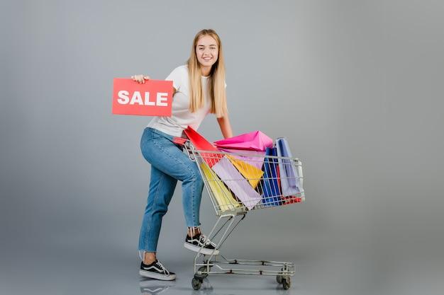 灰色で分離されたカラフルなショッピングバッグと販売サインと手押し車と笑顔の幸せな金髪女