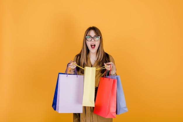 メガネと黄色で分離されたカラフルなショッピングバッグとコートの流行に敏感な若いヨーロッパ人女性