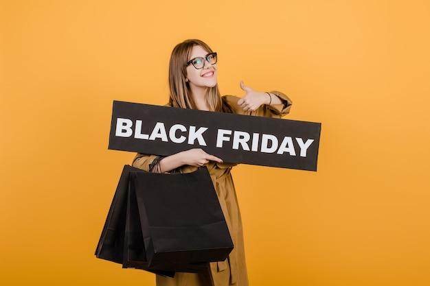 Улыбается женщина в очках с черным знаком пятницу и бумажные сумки, изолированных на желтом