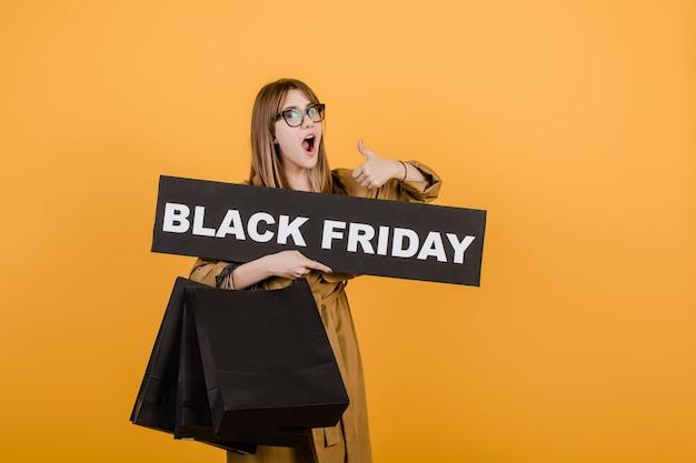 黒金曜日サインと黄色で分離された紙の買い物袋とメガネの女性の笑みを浮かべてください。