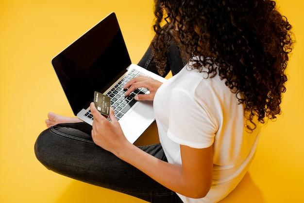 Счастливая африканская чернокожая женщина сидя с компьтер-книжкой и кредитная карточка изолированная над желтым цветом