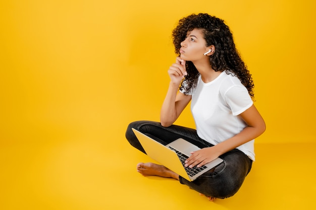 ノートパソコンと黄色で分離されたイヤフォンと座っているかなり若い黒人アフリカ女性
