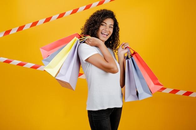 信号テープと黄色で分離されたカラフルなショッピングバッグと美しいアフリカ黒人女性