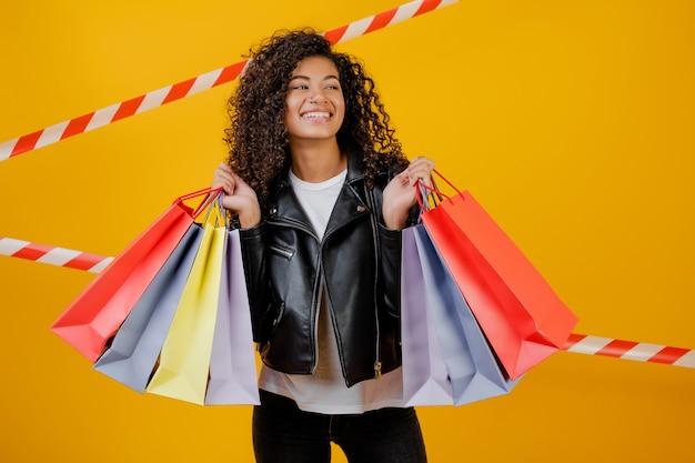 Счастливая модная черная девушка с красочными сумками, изолированных на желтом с сигнальной лентой