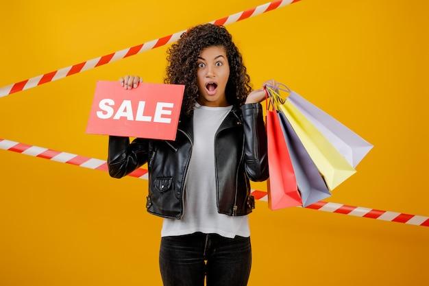 販売サインと信号テープと黄色で分離されたカラフルなショッピングバッグと笑顔の黒の女の子