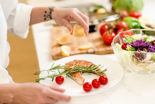 Руки женщины приготовления и подачи рыбы с овощным салатом, зеленью и лимоном