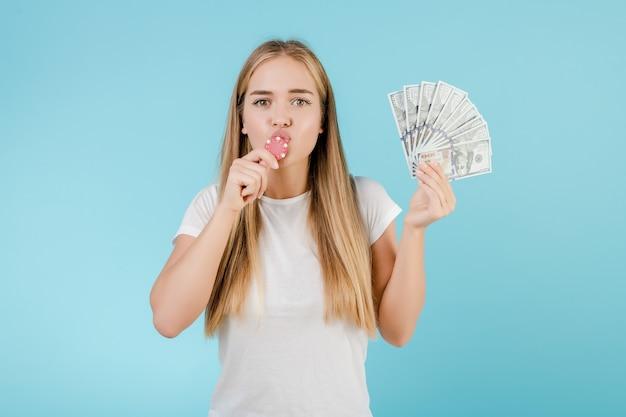 Привлекательная молодая блондинка с покерным фишкой из онлайн-казино и деньгами, изолированными над синим