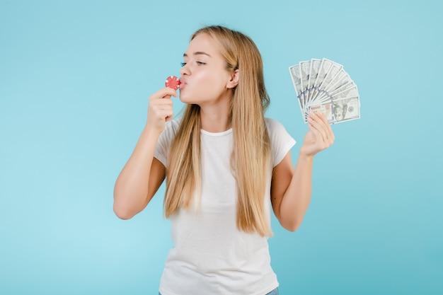 オンラインカジノと青で分離されたお金からポーカーチップを持つ魅力的な若いブロンドの女の子