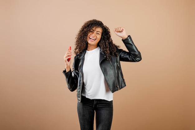 Красивая молодая черная женщина танцует и поет с телефоном в руке, изолированных на коричневый