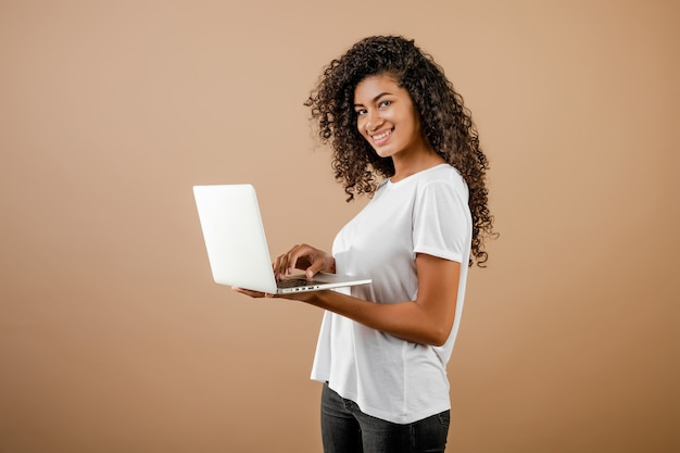 茶色の上分離された手でラップトップを持つ若い美しい黒人女性
