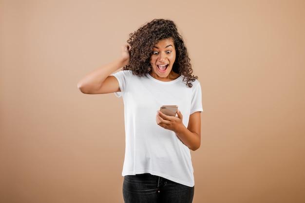 Удивленная взволнованная молодая черная девушка с телефоном в руке, изолированная на коричневом