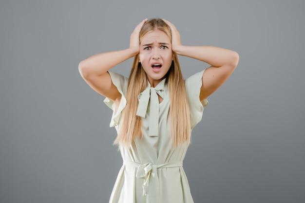 Потрясенная и удивленная эмоциональная девушка держит голову изолированной над серым