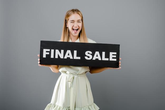Счастливая кричащая белокурая женщина с окончательным знаком продажи изолированная над серым цветом