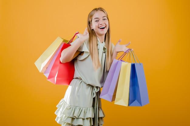 黄色で分離されたカラフルなショッピングバッグと美しい笑顔の女の子