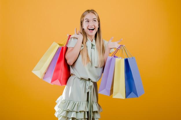 黄色で分離されたカラフルなショッピングバッグに笑みを浮かべて美しい若いブロンドの女性